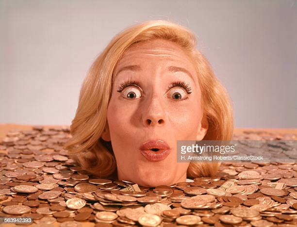 1960s SILLY WACKY EXPRESSION ON FUNNY WOMAN UP TO NECK IN COINS AND CURRENCY DROWNING IN LUCK