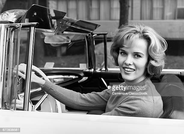 1960s SMILING BLOND WOMAN DRIVING CONVERTIBLE CAR LOOKING AT CAMERA