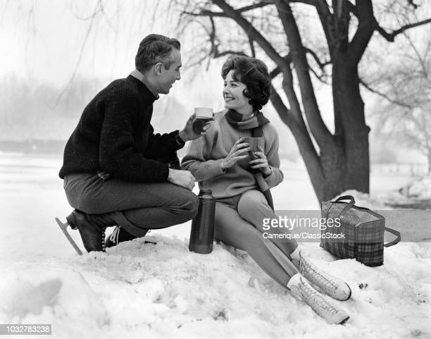1960s SMILING COUPLE IN SNOW WEARING ICE SKATES DRINKING HOT BEVERAGE FROM THERMOS