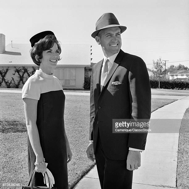 1960s SMILING COUPLE WEARING DRESS CLOTHES STANDING ON NEIGHBORHOOD SIDEWALK