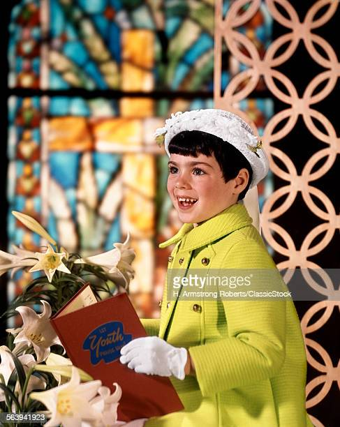 1960s SMILING HAPPY YOUNG GIRL EASTER SUNDAY CLOTHES GREEN COAT WHITE BONNET HAT GLOVES HOLDING CHURCH HYMNAL