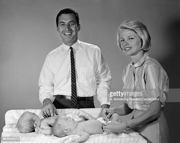 1960s SMILING MOTHER AND FATHER WITH TWIN BABIES ON DIAPER CHANGING TABLE LOOKING AT CAMERA