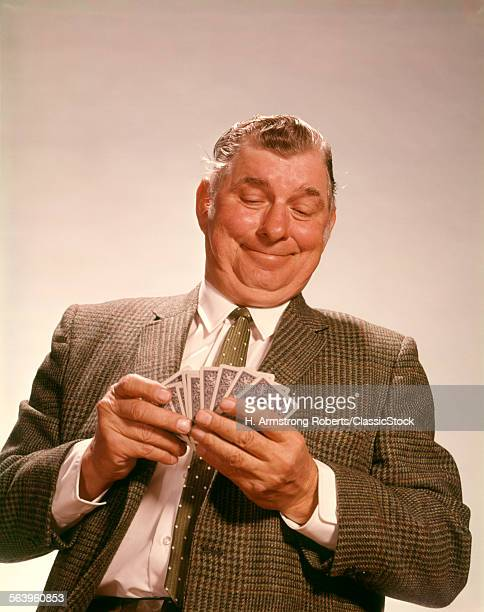 1960s SMILING SATISFIED MAN LOOKING AT HAND OF DEALT PLAYING CARDS