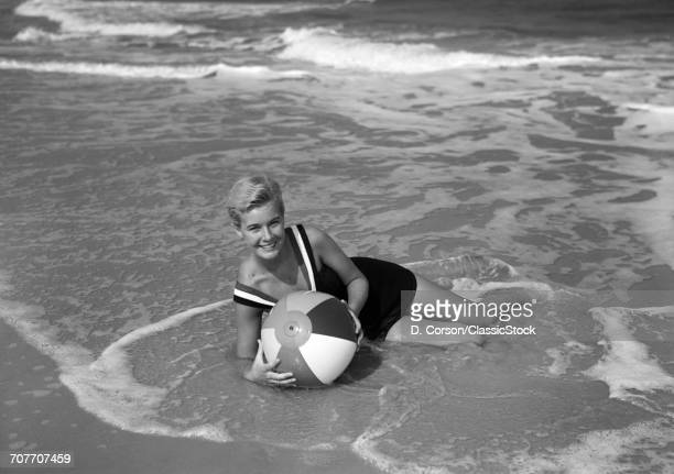 1960s SMILING WOMAN IN BATHING SUIT LAYING IN THE OCEAN SURF HOLDING A BEACH BALL LOOKING AT CAMERA