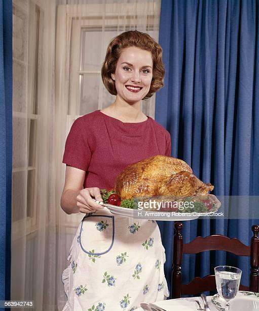 1960s SMILING WOMAN SERVING THANKSGIVING TURKEY DINNER