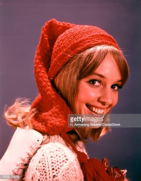 1960s SMILING YOUNG WOMAN WITH ICE SKATES WOOL HAT AND SWEATER LOOKING AT CAMERA