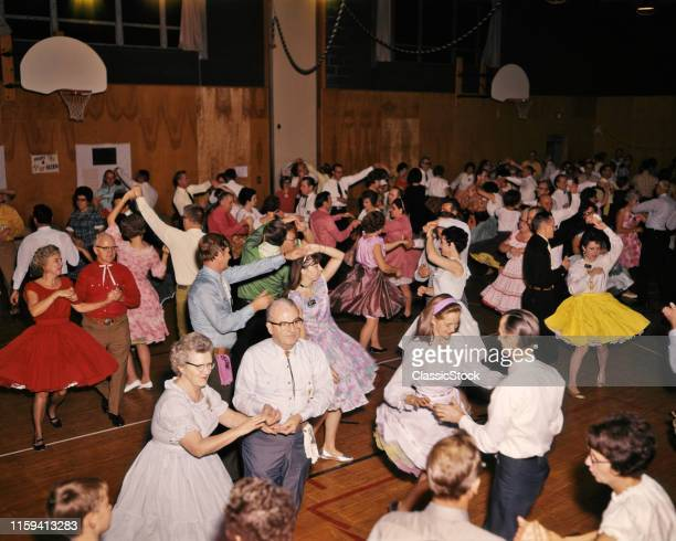 1960s SQUARE DANCE DANCING COUPLES CROWD YOUNG AND OLD SOCIAL EVENT HELD IN GYM