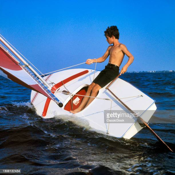 1960s Teenage Boy sailing A Red And White sunfish Boat Heeling In The Wind On Lake Pontchartrain New Orleans Louisiana Usa.
