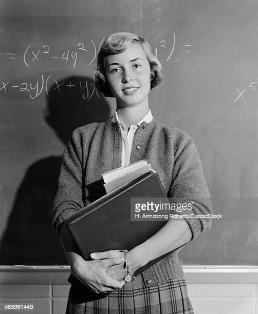 1960s TEENAGE GIRL HOLDING SCHOOL BOOKS STANDING IN FRONT OF BLACKBOARD LOOKING AT CAMERA