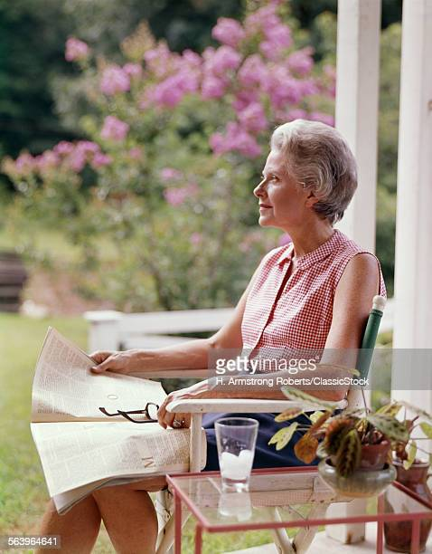 1960s THOUGHTFUL WOMAN SITTING OUTDOORS ON PORCH
