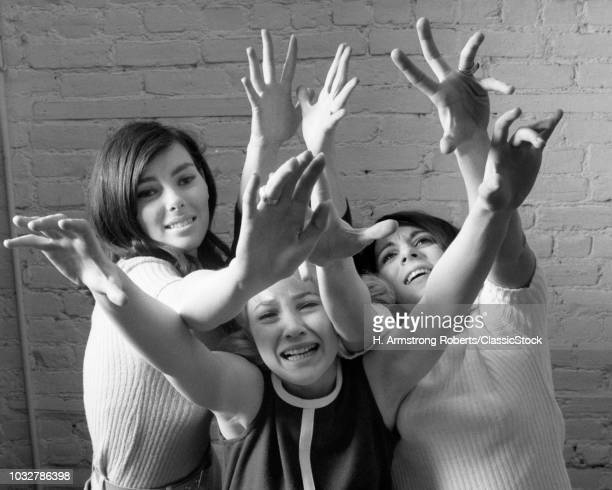 1960s THREE FRENZIED TEENAGE GIRL FANS REACHING OUT AND UP IN ADORATION LOOKING AT CAMERA