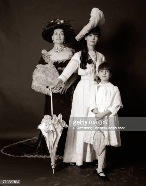 1960s THREE GENERATIONS WOMEN GRANDMOTHER MOTHER DAUGHTER POSED STANDING LOOKING AT CAMERA WEARING 1890s FASHION DRESSES
