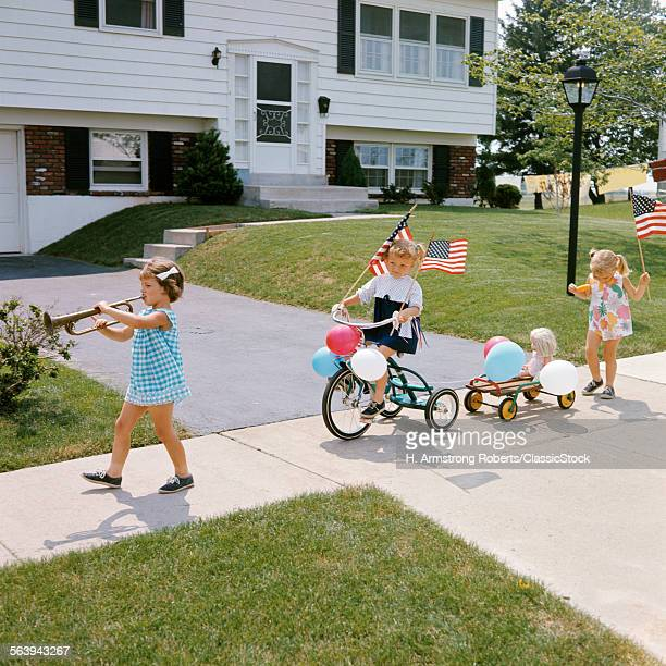 1960s THREE GIRLS DECORATED TRICYCLE SIDEWALK PARADE AMERICAN FLAGS JULY 4TH HOLIDAY SUMMER
