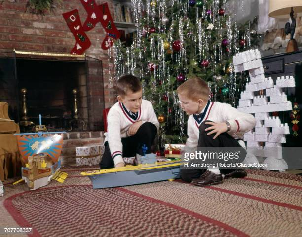 1960s TWO BROTHERS PLAYING WITH TOY MODEL AIRCRAFT CARRIER AND LEGO BLOCKS BY DECORATED CHRISTMAS TREE