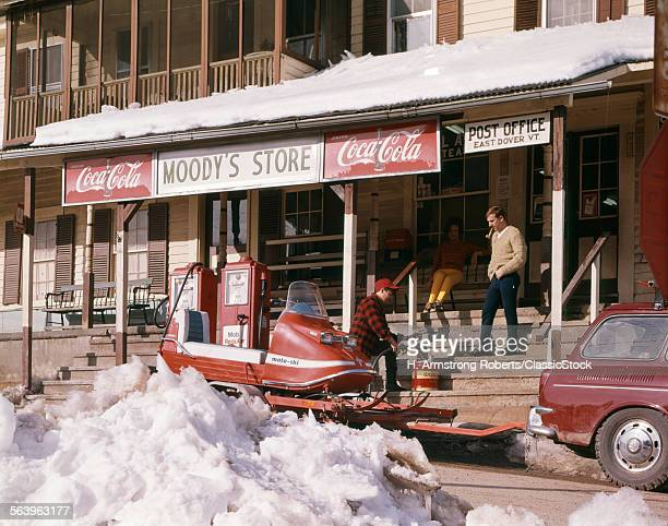 1960s TWO MEN PUMPING GAS FOR SNOWMOBILE ON TRAILER PARKED BY FRONT PORCH OF GENERAL STORE AND POST OFFICE EAST DOVER VT USA