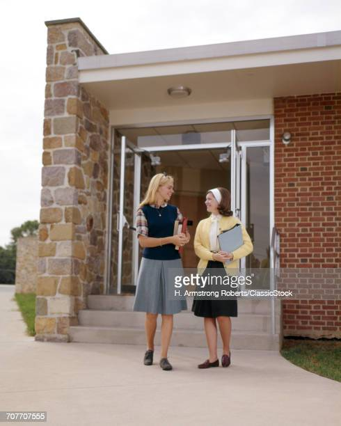 1960s TWO TEEN GIRL STUDENTS TALKING CARRYING BOOKS STANDING FRONT SCHOOL BUILDING
