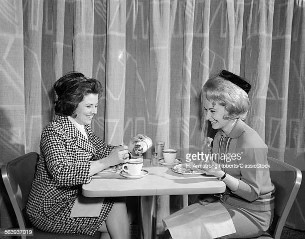 1960s TWO WOMEN HAVING LUNCH IN COFFEE SHOP RESTAURANT