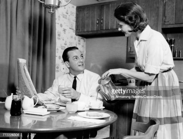 1960s WIFE POURING BREAKFAST COFFEE FOR HUSBAND DRINKING JUICE READING MORNING NEWSPAPER