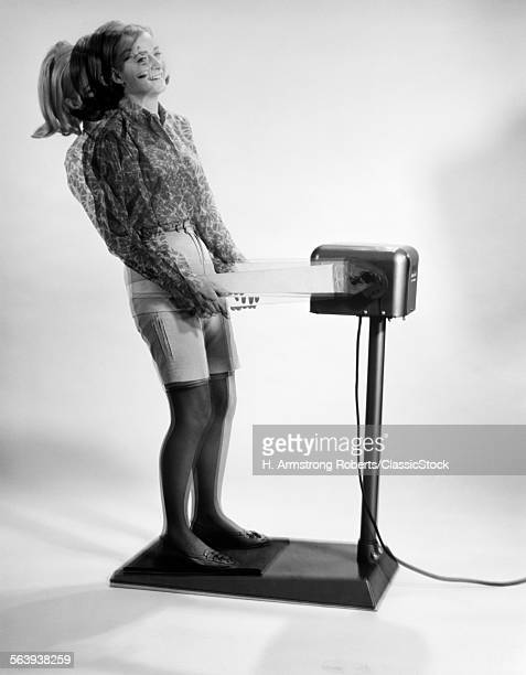 1960s WOMAN MASSAGED BY VIBRATING EXERCISE MACHINE