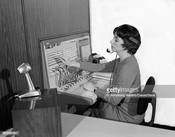 1960s WOMAN OFFICE TELEPHONE SWITCHBOARD OPERATOR WEARING HEADSET TRANSFERRING CALL RECEPTIONIST ANSWERING SERVICE MICROPHONE
