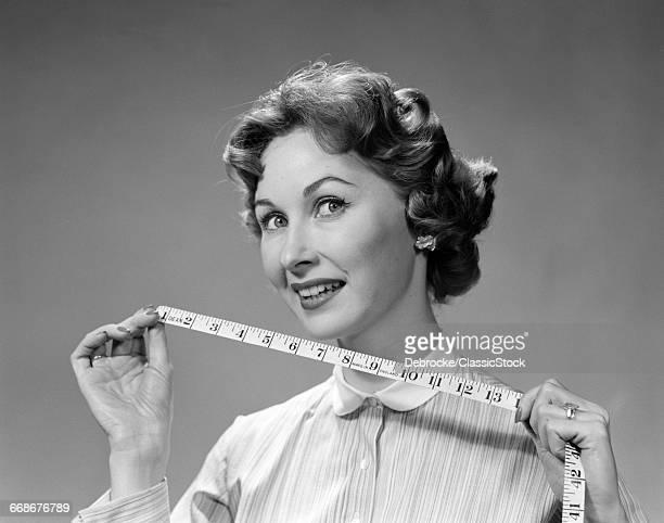 1960s WOMAN PORTRAIT HOLDING MEASURING TAPE