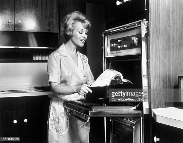 1960s WOMAN WEARING APRON IN KITCHEN PUTTING ROAST INTO THE OVEN