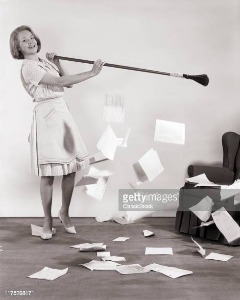 1960s WOMAN WITH BROOM SWEEPING UP PAPERS BILLS MAKING A CLEAN SWEEP STARTING FRESH ANEW