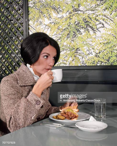 1960s YOUNG WOMAN DRESSED UP TWEED JACKET SIPPING DRINK COFFEE EATING DELI LUNCH SANDWICH