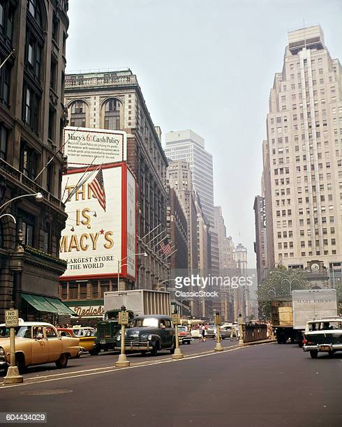 1960s TRAFFIC CARS TRUCKS TAXIS ON BROADWAY AT HERALD SQUARE AND MACY'S DEPARTMENT STORE MANHATTAN NEW YORK CITY USA