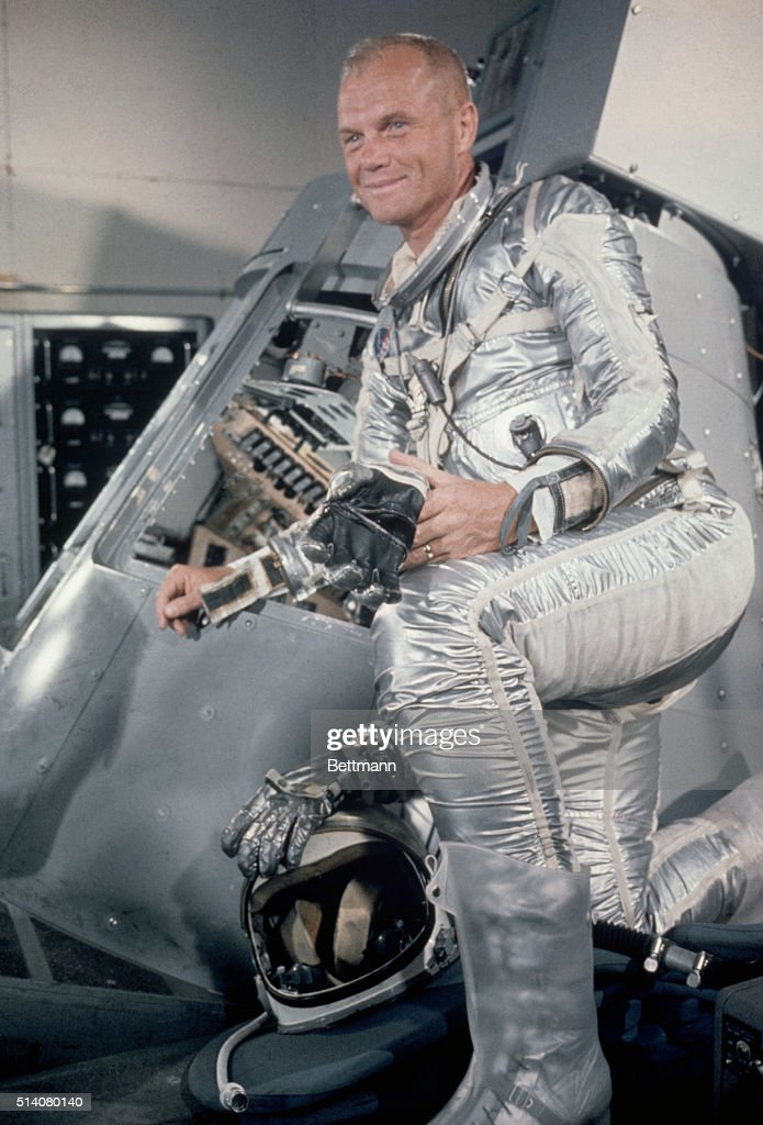 John Glenn Standing Beside a Mercury Capsule : News Photo