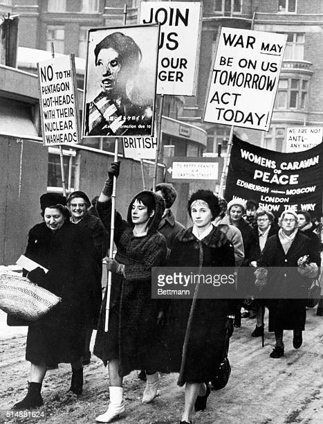 London, England: Heading a procession of women on an anti-bomb march through the ice and slush of London, are - left to right: Mrs. Diana Collins,...