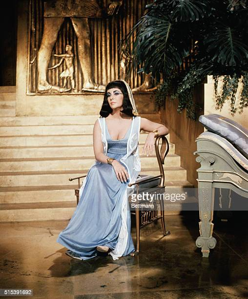 Elizabeth Taylor as Cleopatra is shown seated on a chair in front of a stairwell on the set in Rome where the movie is being shot