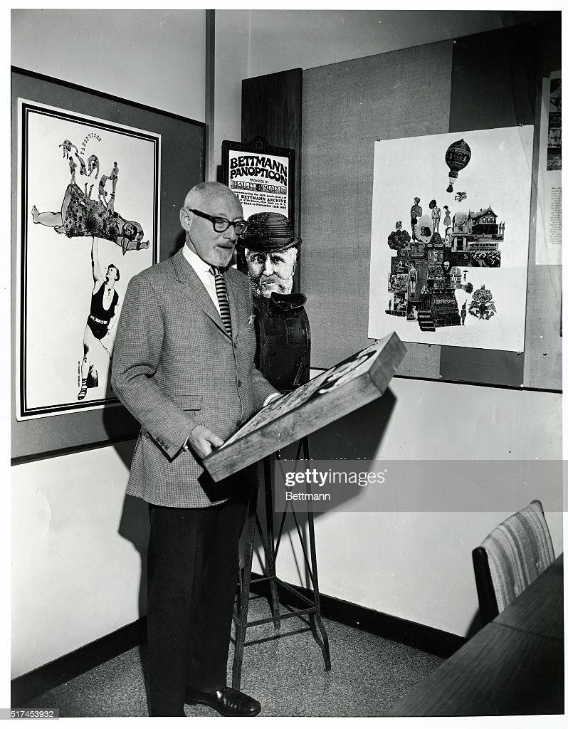 New York, NY-Otto Bettmann stands before 'Bettmann Panopticon' holding a framed illustration.