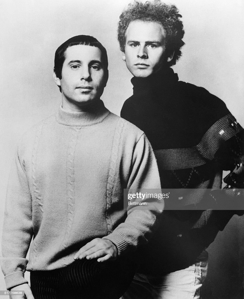 Paul Simon and Art Garfunkel, of the Simon & Garfunkel singing team, pose in a standing, waist-up, studio portrait.