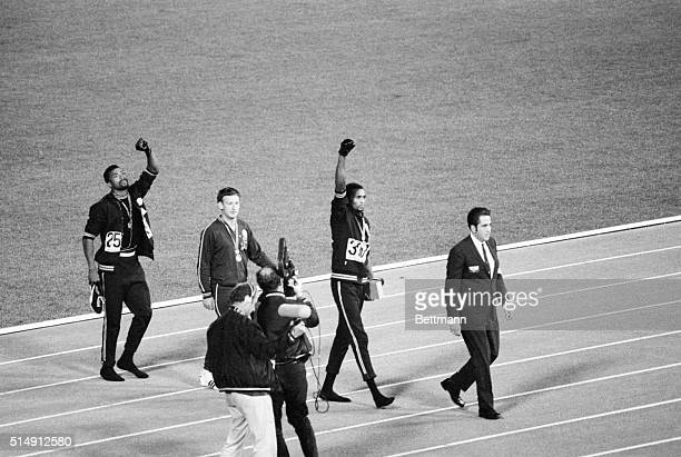 Mexico City, Mexico- Tommie Smith, center, and John Carlos, right, of the United States, raise gloved hands after receiving their Olympic Medals for...