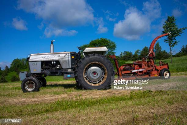 Era White Field Boss tractor with an attached hay cutter lies idle in a field in Charlotte, Vermont on June 14, 2019.