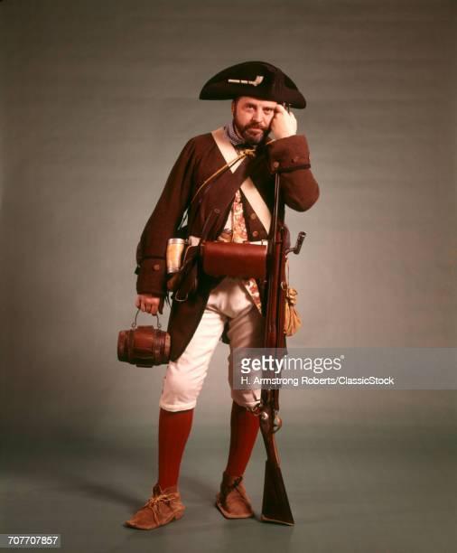 1970s 1776 AMERICAN REVOLUTION HISTORICAL REENACTOR MILITIA SOLDIER TRICORN HAT FLINTLOCK MUSKET AND BAYONET LOOKING AT CAMERA