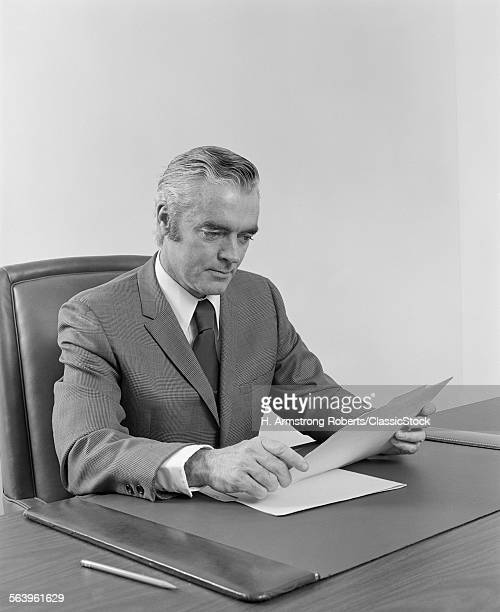 1970s 1960s BUSINESSMAN EXECUTIVE MIDDLE AGED SITTING AT DESK READING PAPERS