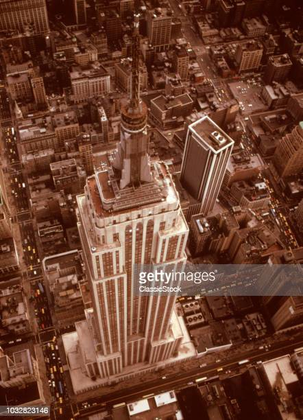 1970s AERIAL SHOT FROM HELICOPTER LOOKING DOWN FULL LENGTH OF EMPIRE STATE BUILDING MIDTOWN MANHATTAN NEW YORK CITY NY USA