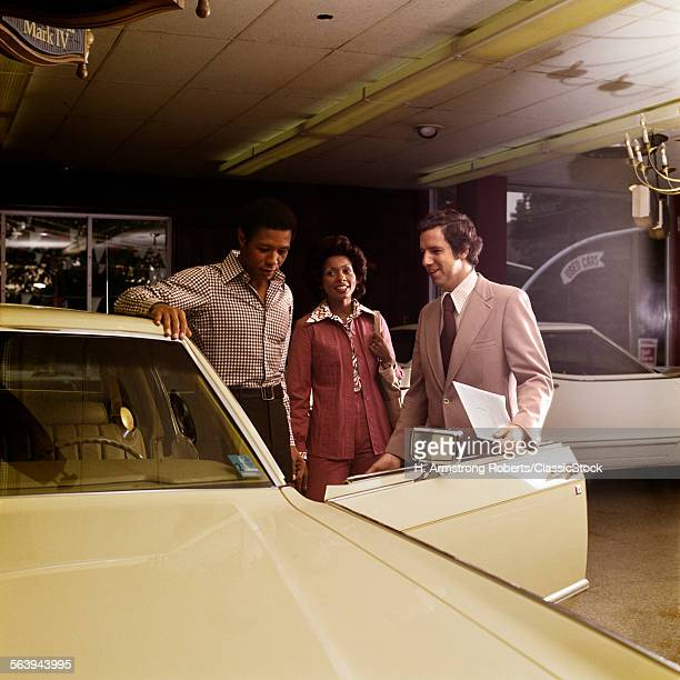 1970s AFRICAN AMERICAN COUPLE WITH SALESMAN AUTOMOBILE SHOWROOM