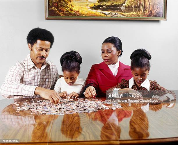 1970s AFRICAN AMERICAN FAMILY FATHER MOTHER TWO DAUGHTERS SITTING AT TABLE DOING JIGSAW PUZZLE