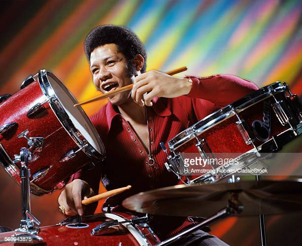 1970s AFRICAN AMERICAN MAN MUSICIAN PLAYING DRUMS STROBE LIGHT EFFECTS BEHIND HIM IN DISCO CLUB
