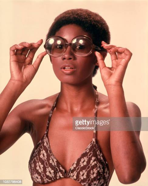 1970s AFRICAN AMERICAN WOMAN WEARING BIKINI BATHING SUIT TOP PUTTING ON LARGE LENS SUNGLASSES LOOKING AT CAMERA