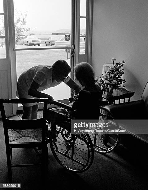 1970s ANONYMOUS SILHOUETTED NURSE HELPING ELDERLY PERSON SITTING IN WHEELCHAIR ALL IN SILHOUETTE