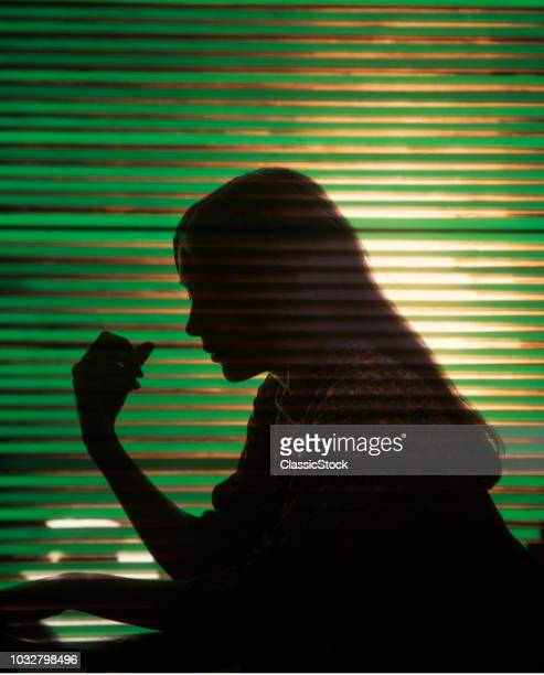 1970s ANONYMOUS WORRIED WOMAN GIRL PROFILE SILHOUETTED AGAINST GREEN WINDOW BLINDS