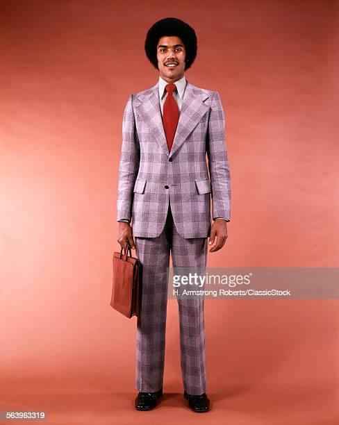 1970s ARICANAMERICAN ETHNIC BUSINESSMAN PORTRAIT FULL FIGURE HOLD BRIEFCASE IN GLEN PLAID SUIT MAN FASHION AFRO HAIR