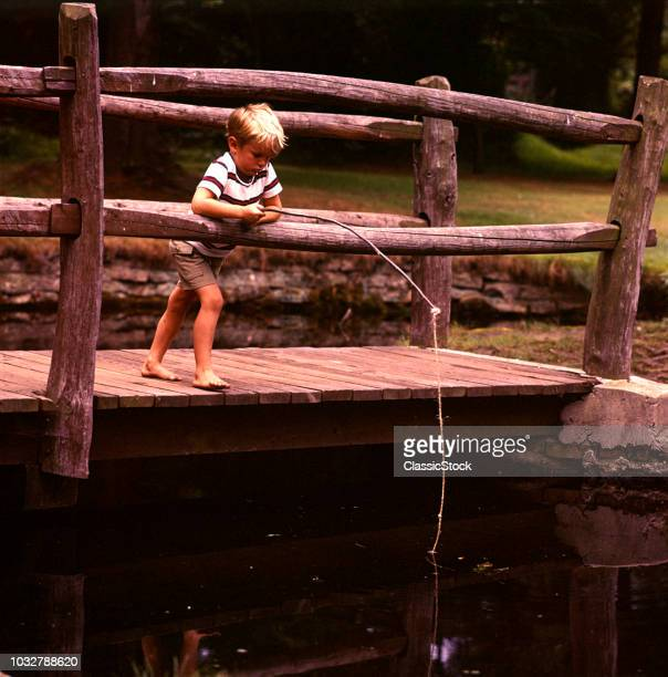 1970s BAREFOOT BLOND BOY FISHING IN POND OFF OF WOODEN BRIDGE