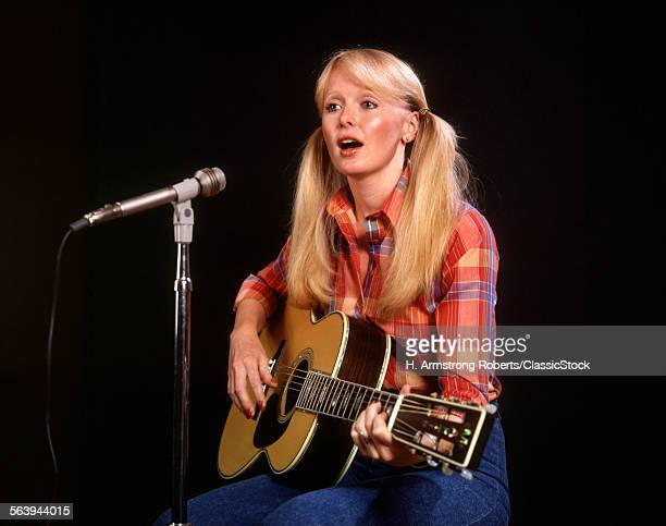 1970s BLOND BLONDE YOUNG WOMAN PIGTAILS PLAID SHIRT JEANS PLAY GUITAR SINGING MICROPHONE FOLK SINGER SINGERS