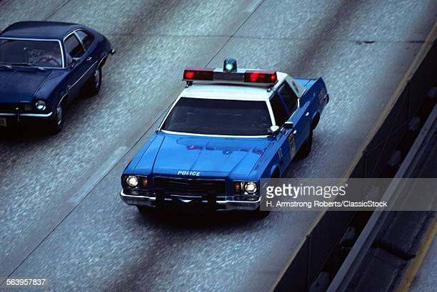 1970s BLUE AND WHITE NEW YORK CITY POLICE CAR ON HIGHWAY FROM ABOVE