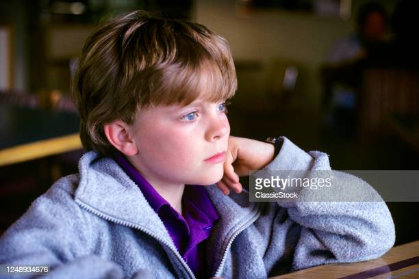 1970s Blue Eyed Preteen Boy Student In Classroom Pensive Facial Expression Resting Head On Hand Gazing Into The Future
